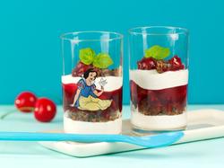 Quarkspeise mit Pumpernickel, Kirschen und Schokoraspeln in einem Glas, auf dem Schneewittchen drauf ist